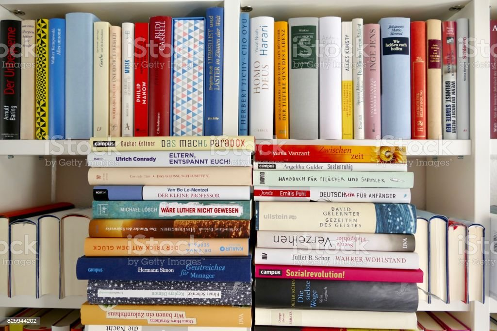 Filled books shelf close up with a stack of books leaning at it stock photo