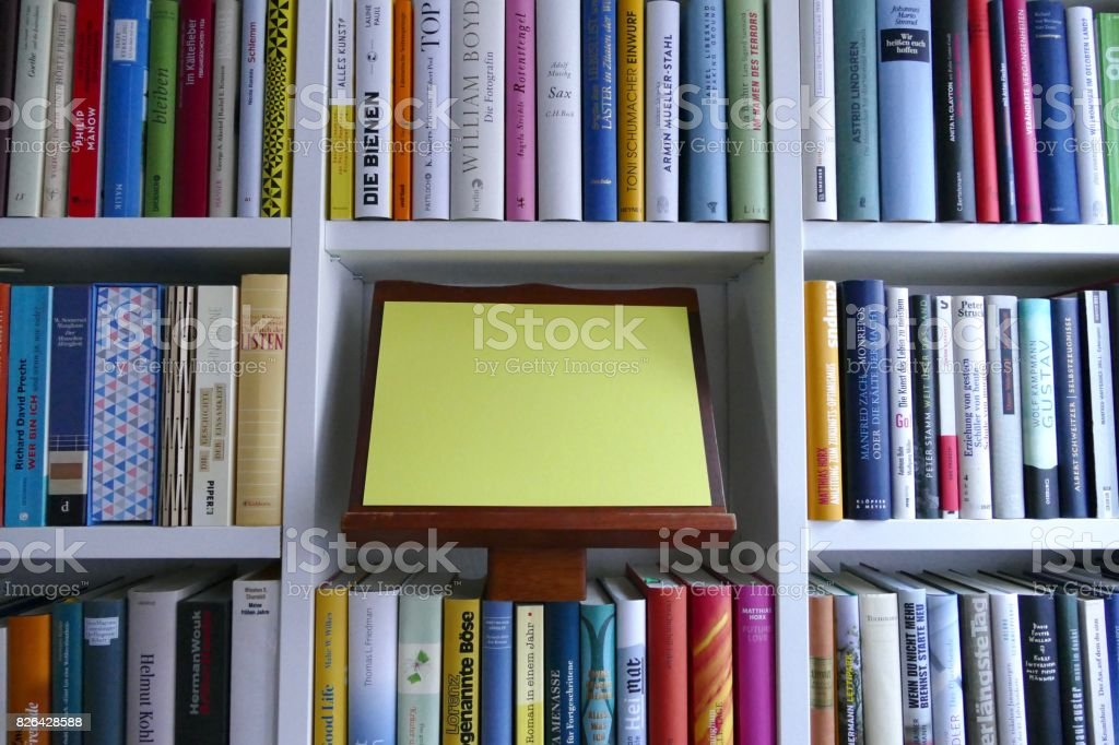 Filled Books Shelf Close Up With A Yellow Empty Paper Space For Copy Royalty