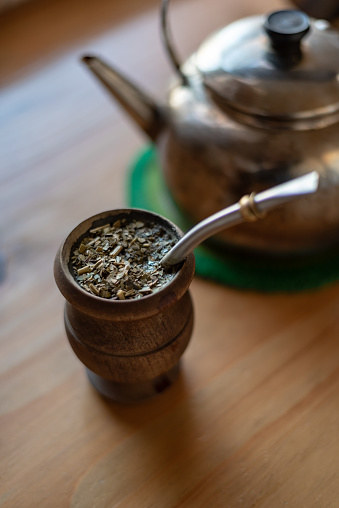 Filled mate with a kettle on a watermelon trivet over a wooden counter