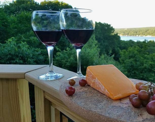 2 Filled Red Wine Glasses with Cheese and Grapes to Side, with Water Views in Background stock photo