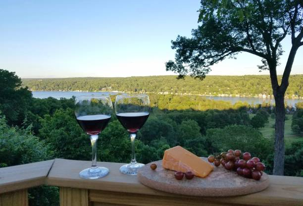 2 Filled Red Wine Glasses with Compliment of Cheese and Grapes in a Rustic, Water View Background, Nearing Dusk stock photo