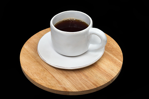 Filled white cup and sauser stading on a wooden stand isolated on black background. Ceramic white tea pair. Cup of tea. Cup of coffee.