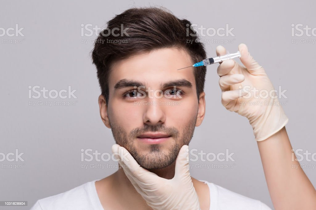 Filler injection for male face in beauty clinic stock photo