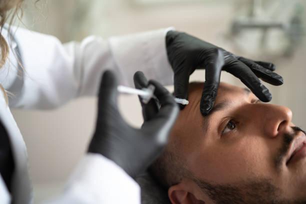 füllerspritzen für männliches gesicht in schönheitsklinik - nadeldesigns stock-fotos und bilder