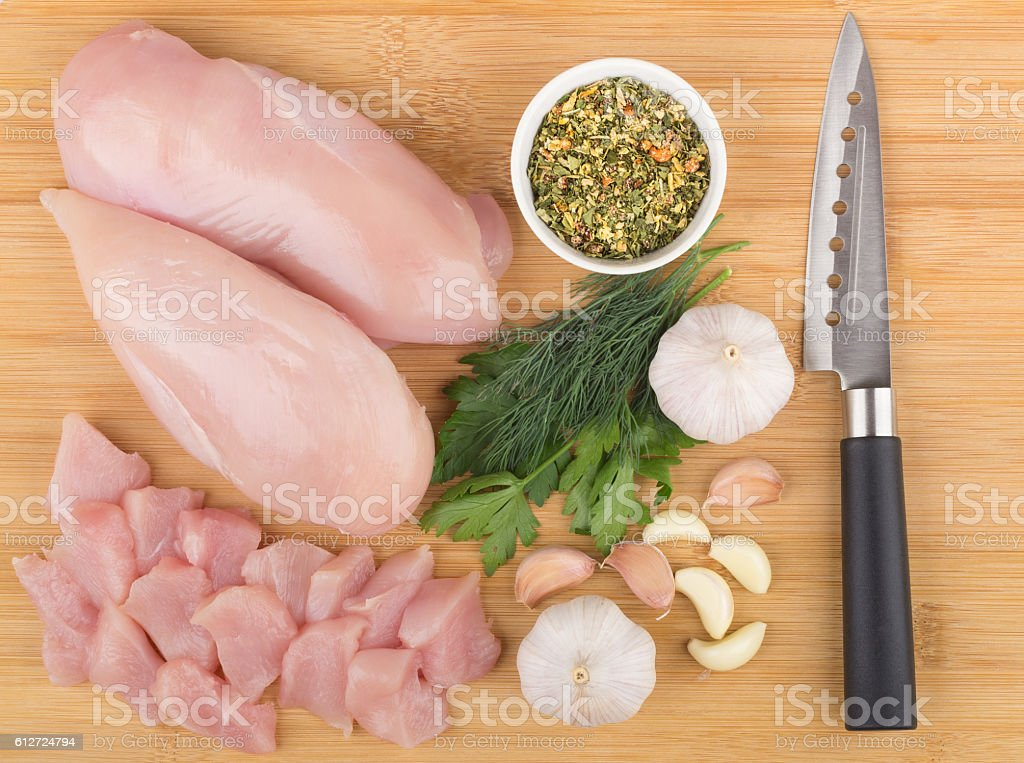 Fillet of chicken breast, greens, spices and kitchen knife - foto de acervo