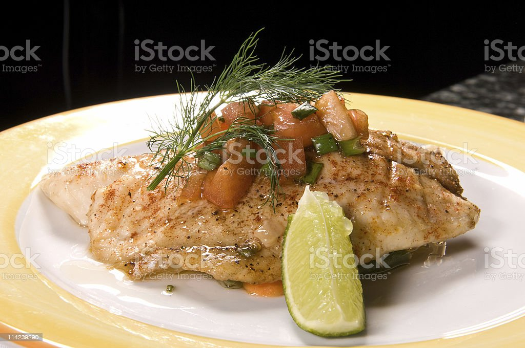 Fillet of fish with slice of lemon on a plate royalty-free stock photo