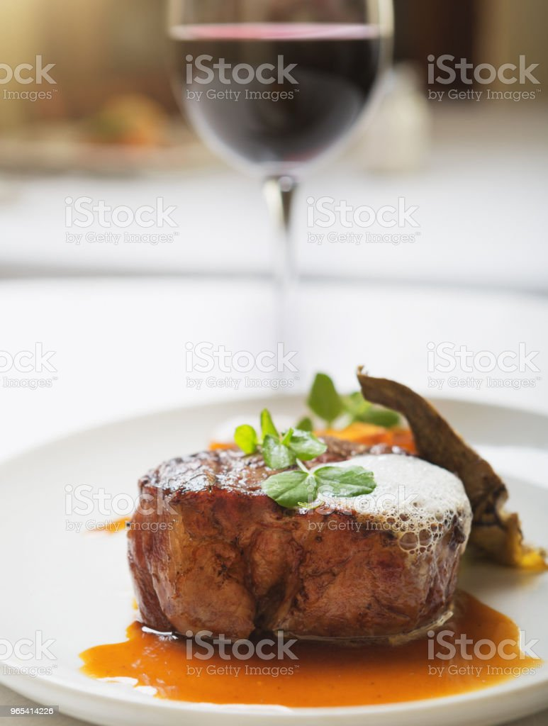 Fillet steak in pool of delicious juices, red wine alongside royalty-free stock photo