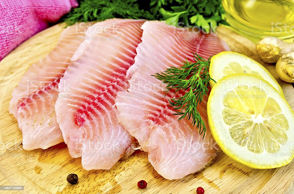 Fillets tilapia with oil and lemon stock photo