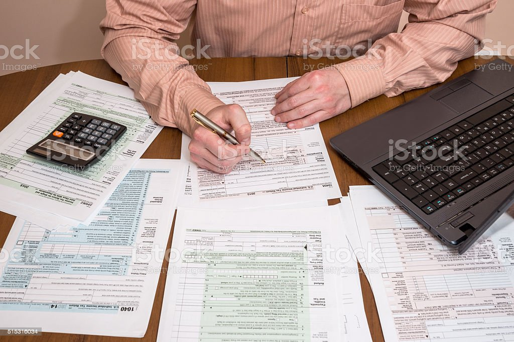 Filling 1040 tax form wtih laptop stock photo