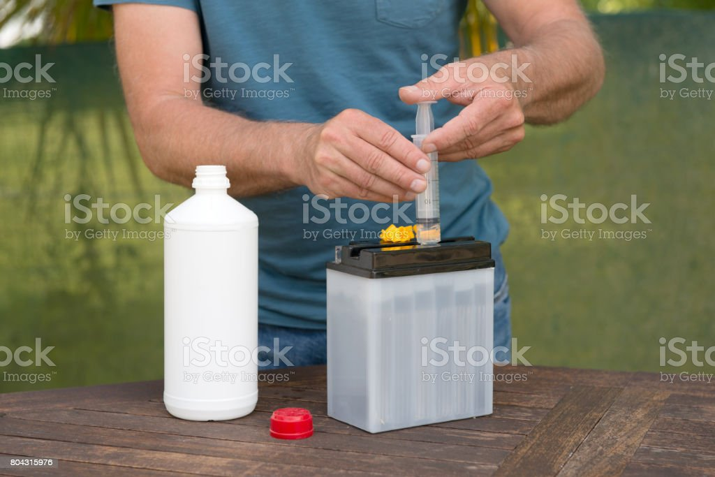 Filling a battery with acid stock photo