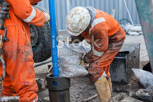 London, England - March 10, 2015: Filling a Borehole with aggregate. Two workmen working on a pipe in a borehole. Workmen in orange overalls and white hardhats outside.  they have yellow gloves and boots and are next to a borehole drilling rig which is the green upright bar.  One man holding the pipe steady and the other pours in aggregate