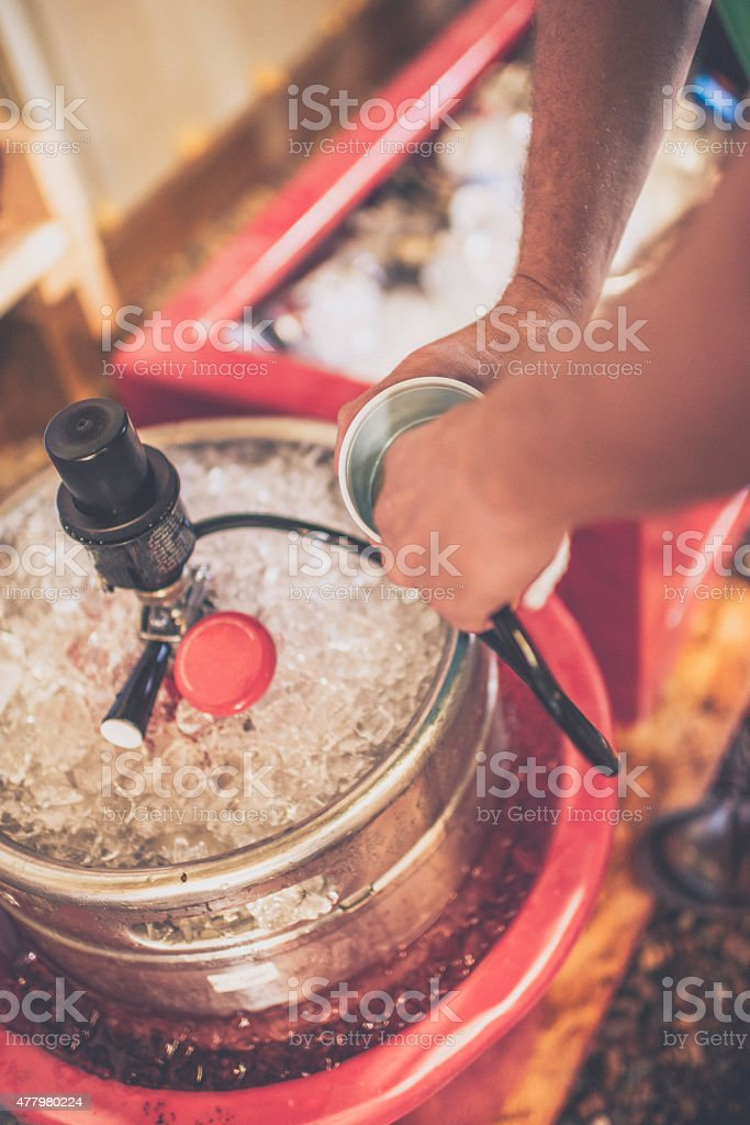 Filling a cup with beer from a keg. Summer party. stock photo