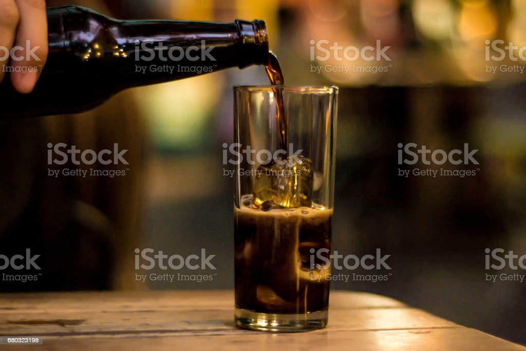 Filling a glass with drink stock photo