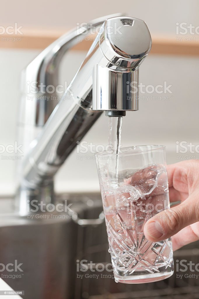 Filling a glass with water stock photo