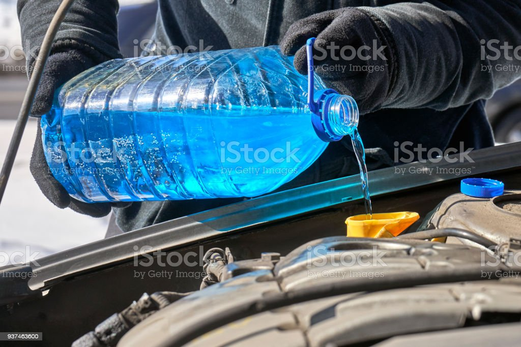 Filling a windshield washer tank of a car by antifreeze close up stock photo