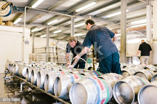 Staff fill aluminium beer kegs on long trolleys, with a local real ale, ready for distribution at a traditional Devon brewery warehouse, Otter Brewery, Ottery St. Mary, Devon, UK