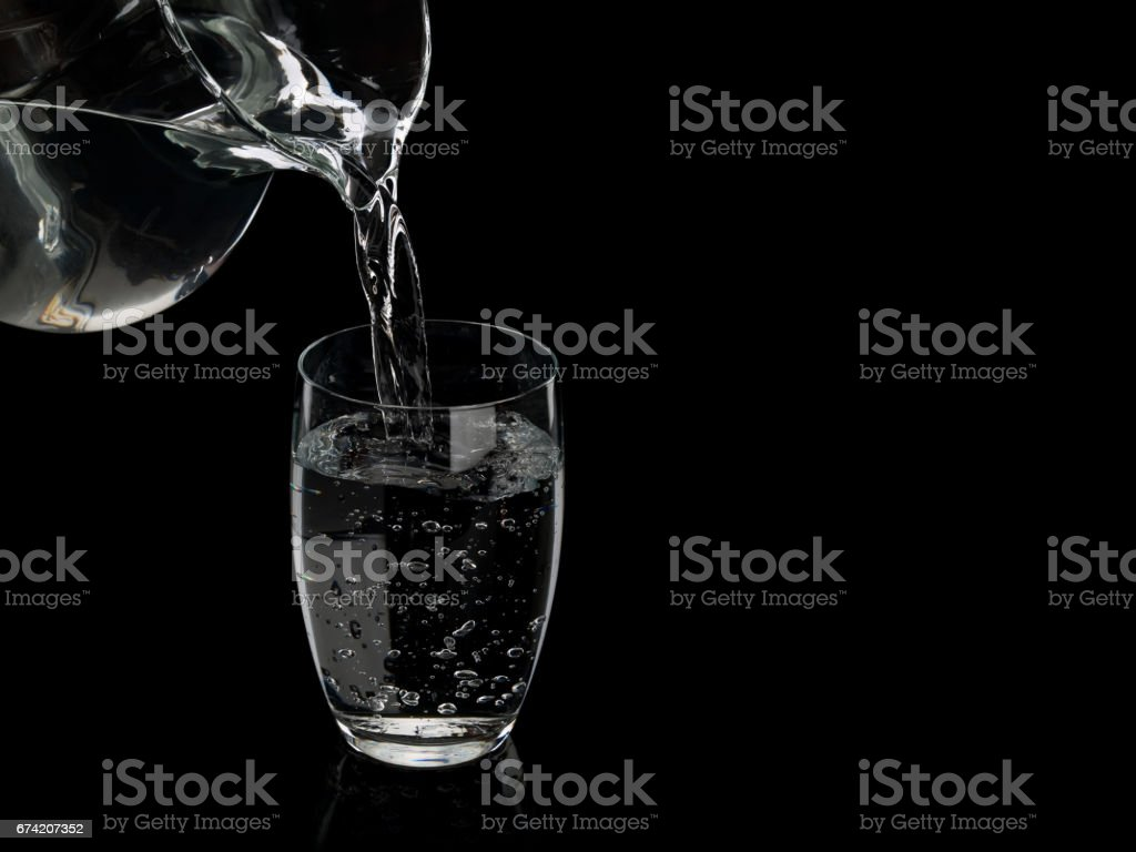 Filling by water of a glass from a glass jug stock photo