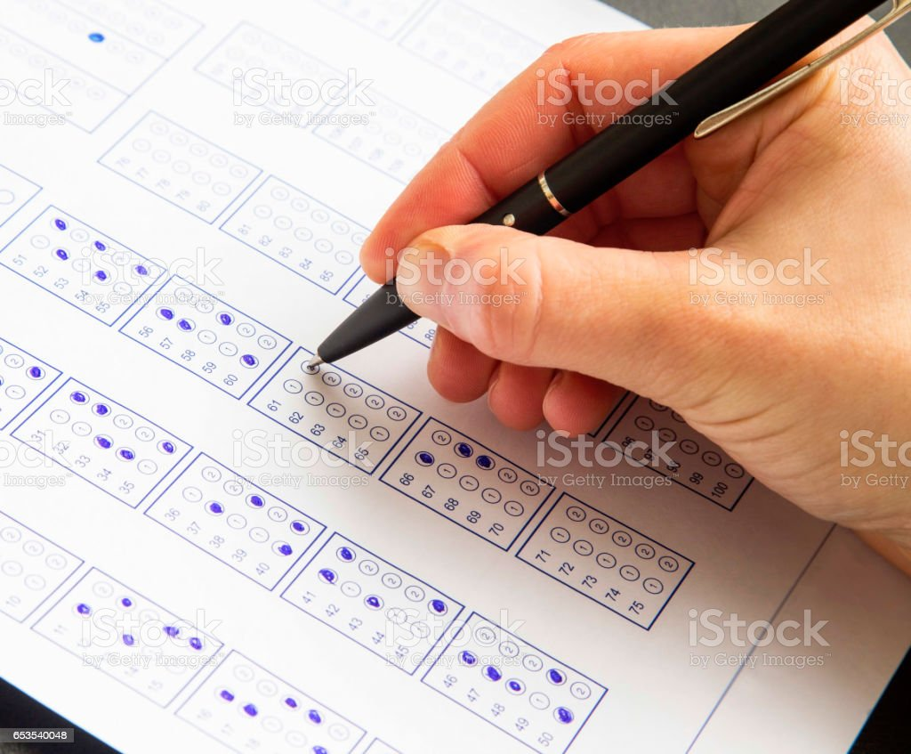 Filling exam questionnaire,hand with pen marking right answers at school or university stock photo