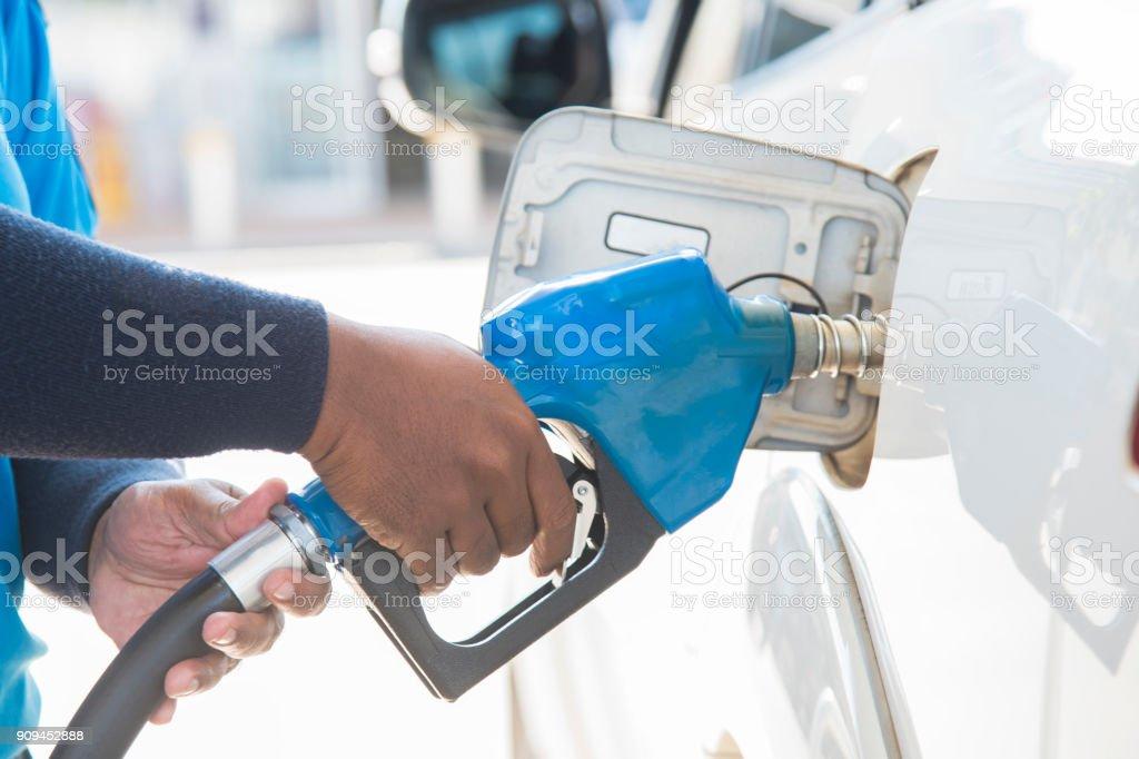 Gás de enchimento na estação. Reabasteça com óleo, gasolina, veículo a diesel. Mão, encher o carro com combustível. - foto de acervo