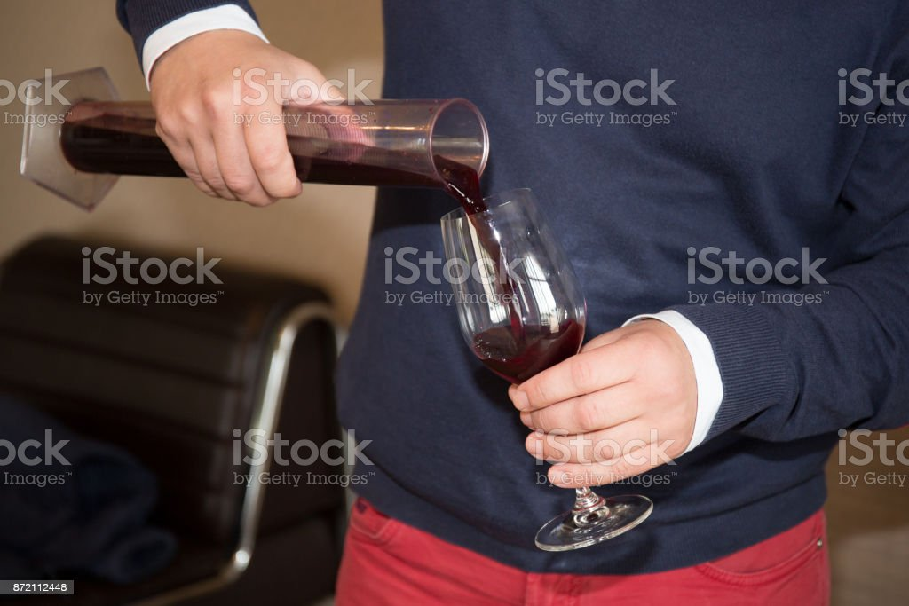 Filling glass decanter with red wine for aeration stock photo