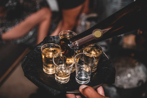 Filling glasses with Tequila Filling glasses with Tequila tequila shot stock pictures, royalty-free photos & images