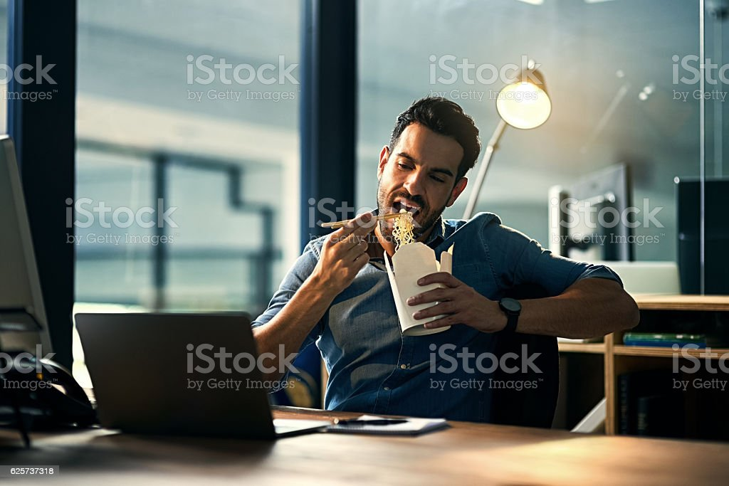 Shot of a young businessman working at night and eating takeout at...