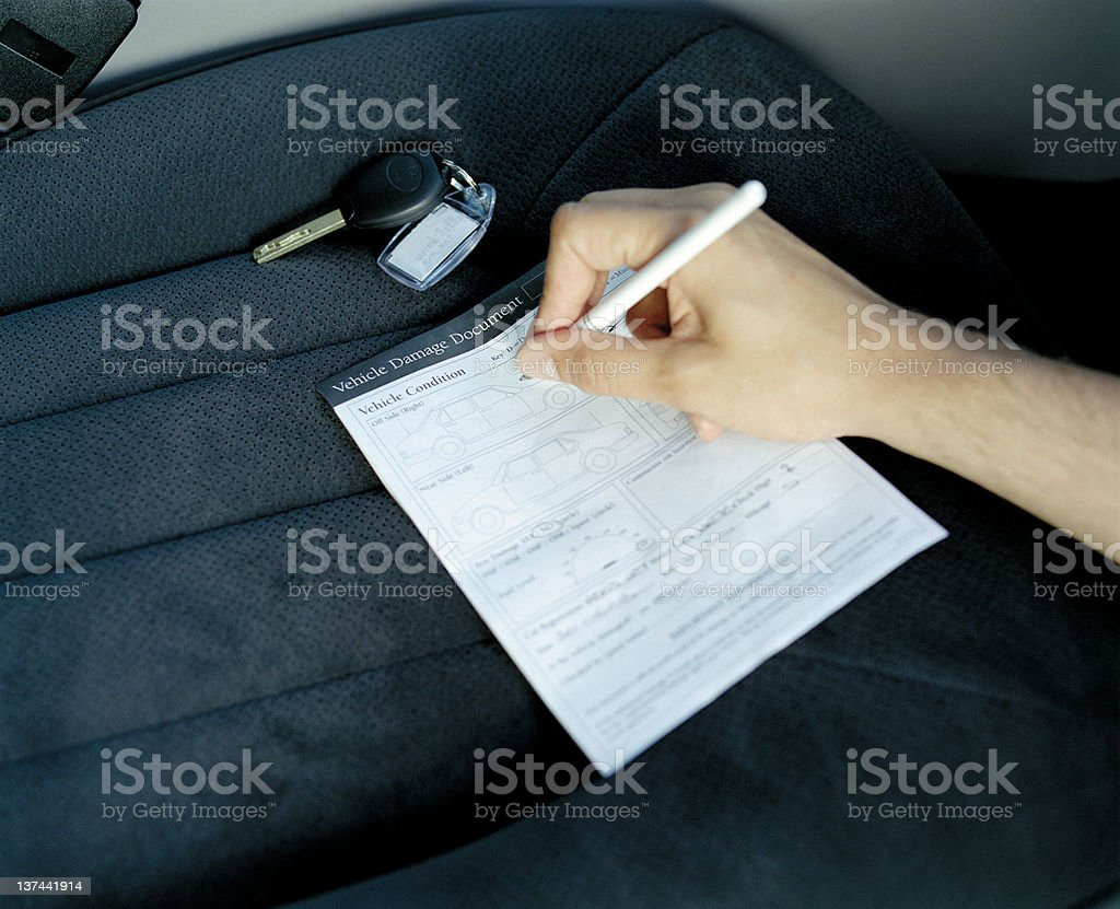 Filling in Vehicle damage document (no personal details recorded) royalty-free stock photo