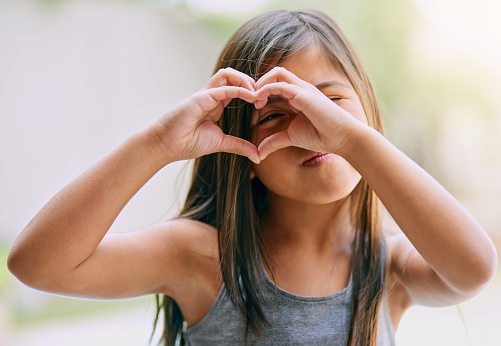Portrait of a little girl making a heart gesture with her hands