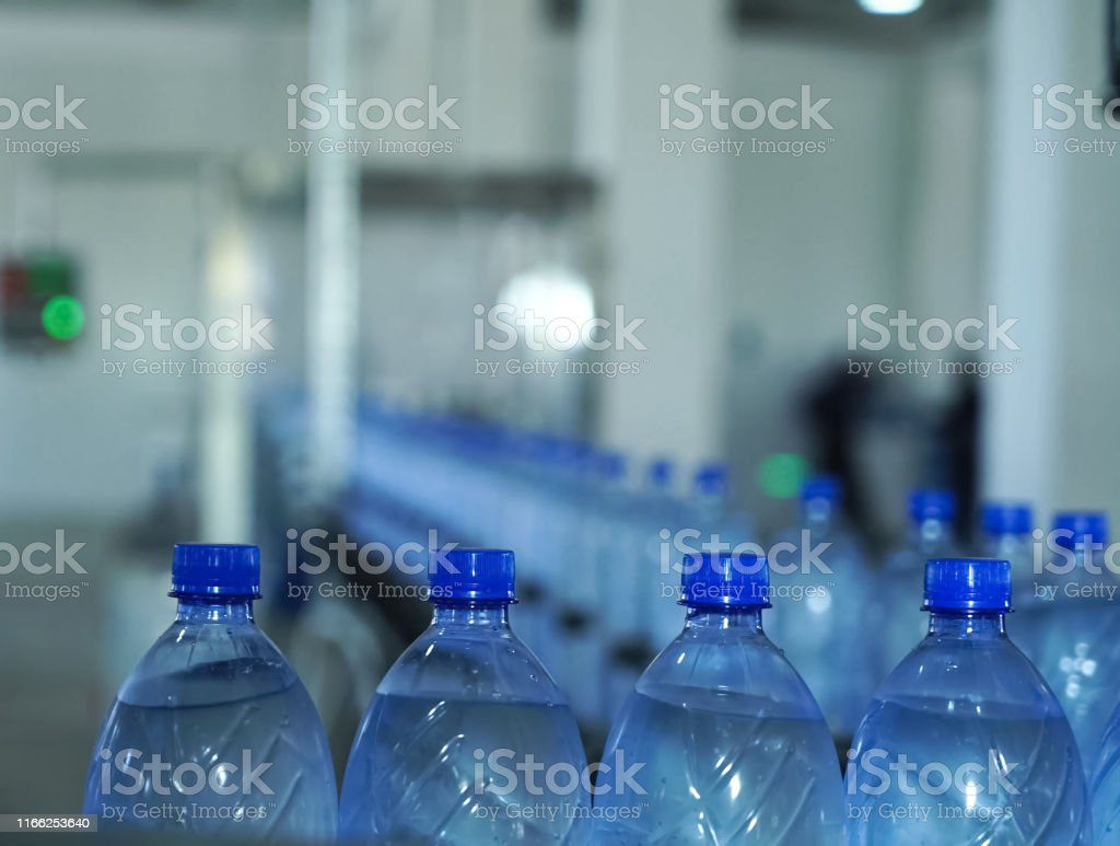 Filling line of sparkling water in a pet bottle. Mini factory for...