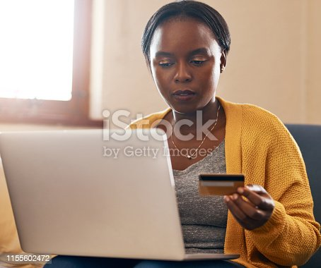 Cropped shot of an attractive mature woman holding a credit card while using her laptop in the lounge