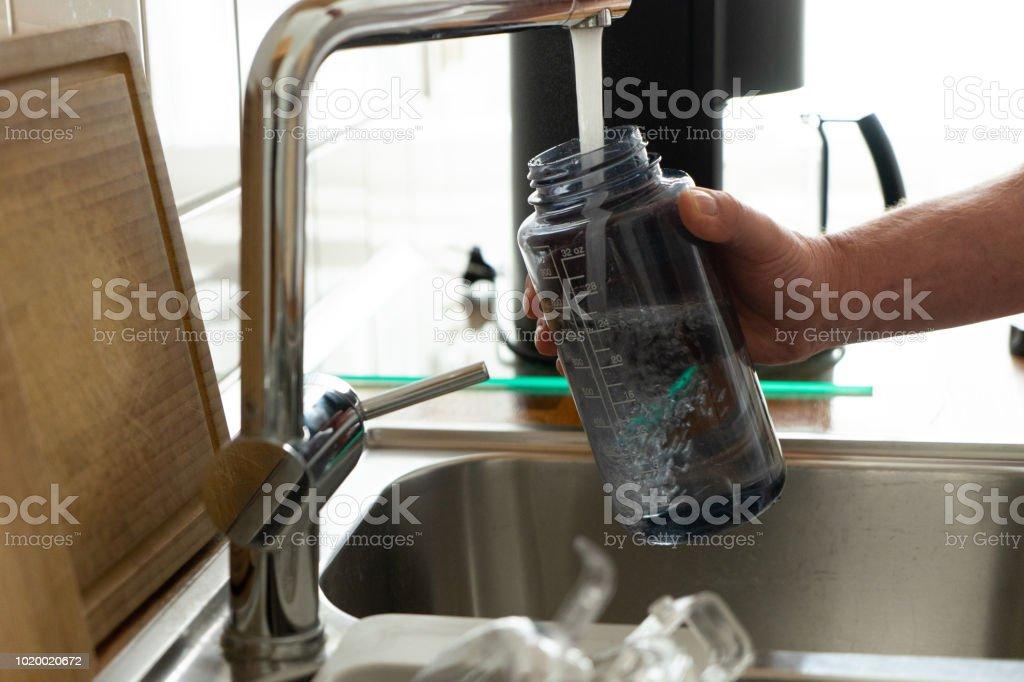 Filling sport water bottle royalty-free stock photo
