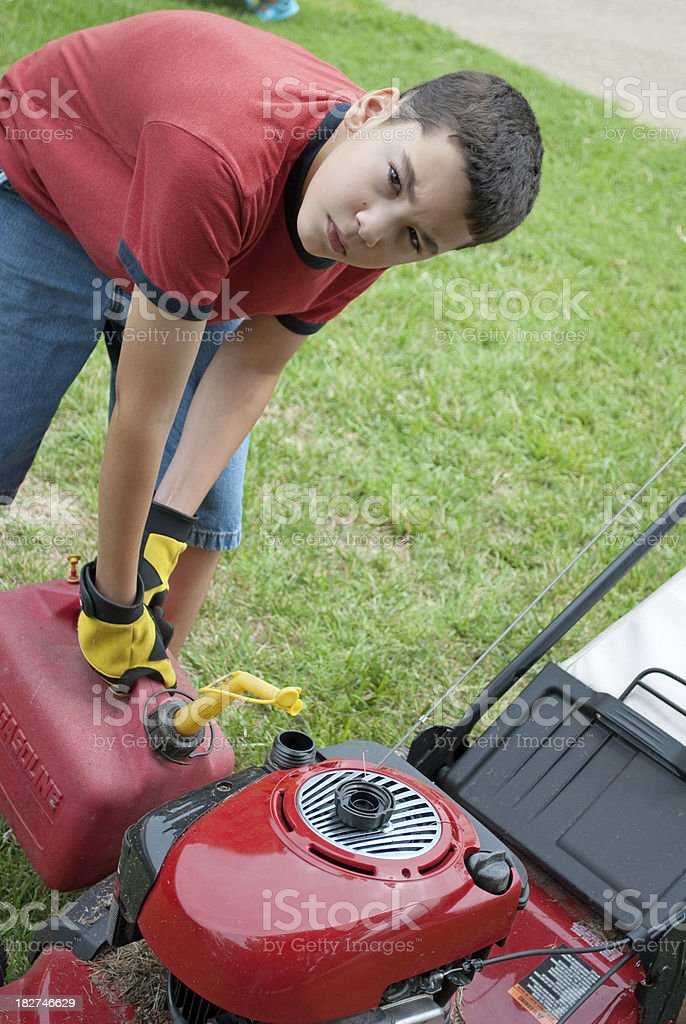 Filling the Mower - Hard Working Kid royalty-free stock photo