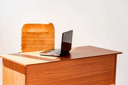 A wooden table on which stands a laptop with a leather chair next to it. The entire space is filled with morning, bright sun
