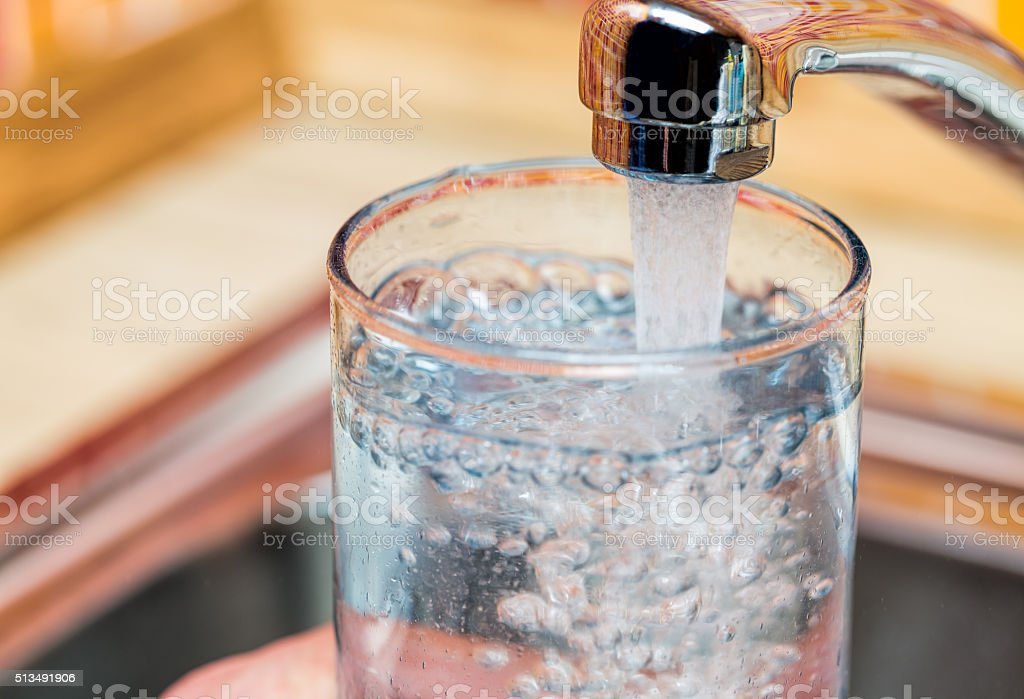 Filling up a glass with drinking water from kitchen tap stock photo