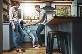 Shot of a family playing together in the kitchen at home