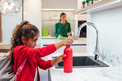 A young schoolgirl in her uniform fills up her water bottle before heading to school.