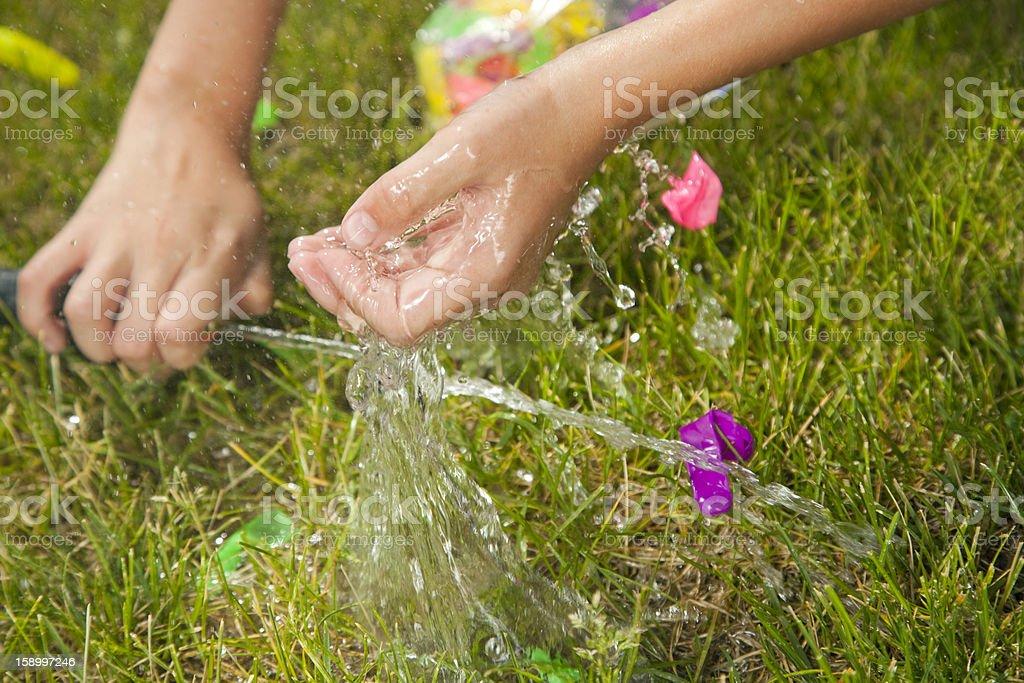 Young boy fills a green water balloon with garden hose.