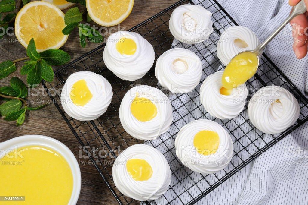 Filling with a lemon kurd, a delicate, crispy mini-dessert 'Pavlova' on the rack stock photo