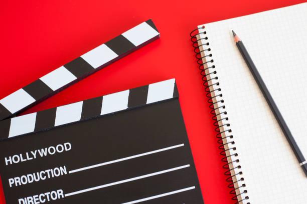 filmklapper und stift notizblock auf rotem hintergrund - drehbuchautor stock-fotos und bilder