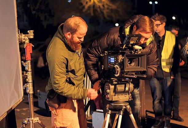 Film crew on location, night shoot. Cinamatographer with 4k camera stock photo
