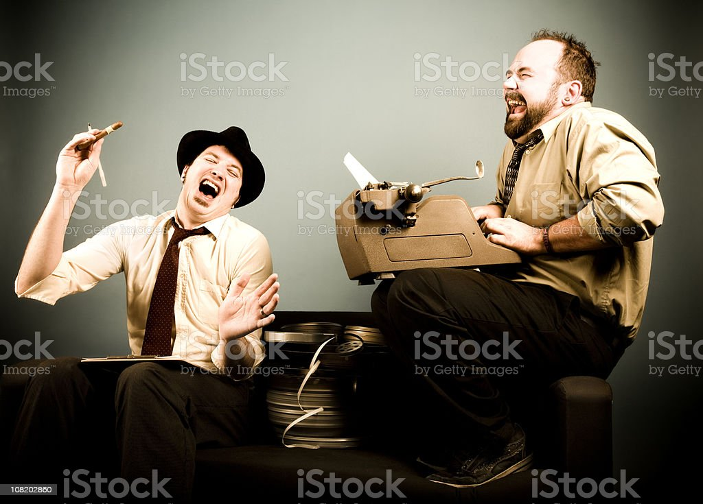 Film Critics: Laughing and Typing royalty-free stock photo