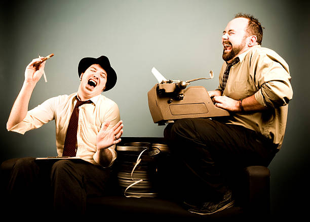 Film Critics: Laughing and Typing stock photo