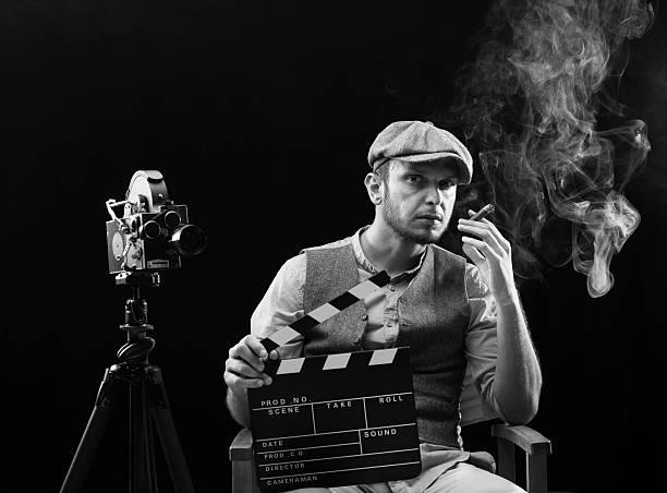 film director rauchen zigarre hinter die kamera. - klappe hut stock-fotos und bilder