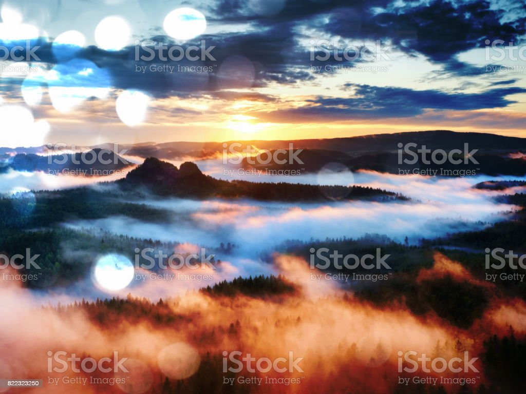 Film effect.  Red daybreak. Misty daybreak in a beautiful hills. Peaks of hills are sticking out from foggy background, stock photo