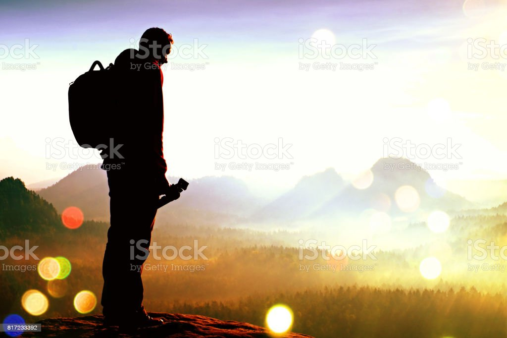 Film grain. Silhouette of photographer overlooking a blanket of fog over valley to sun stock photo