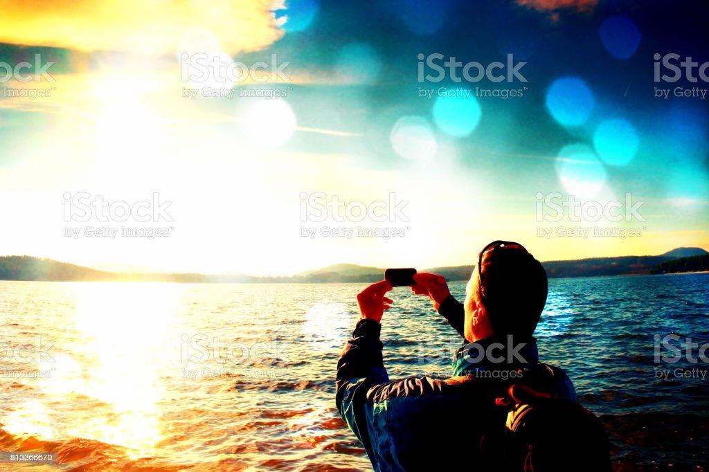 Filmkorn.  Hohen Ingwer Haare Mann Tourist unter Fotos oder Videos mit dem Handy. Sonnigen Herbsttag am Meer Küste – Foto