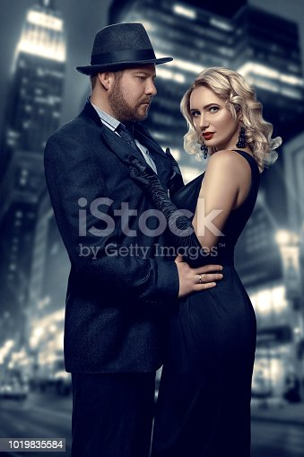 istock Film noir. Detective man in a raincoat and hat and a dangerous woman with red lips in black dress. Couple stands against the background of the night city 1019835584