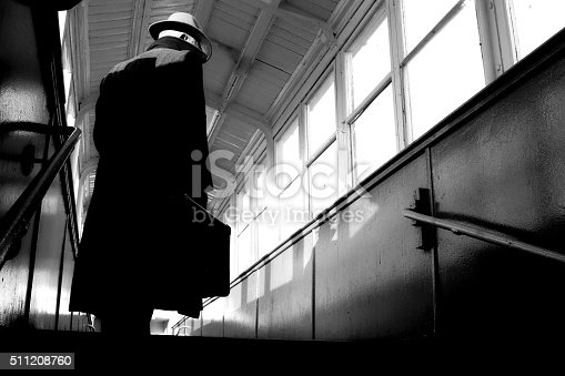 Film Noir style gangster or detective ,man is wearing a fedora hat and trench coat, he is carrying a suitcase.