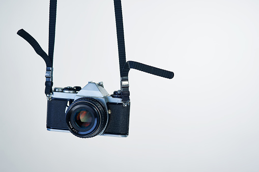 Studio shot of a camera hanging by its strap