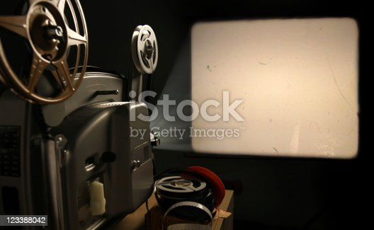 A vintage 8mm film projector projects a blank image with film dust and scratches onto a wall beside a stack of film reels